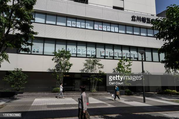 People wearing face masks walk past Tachikawa Sogo Hospital where posters reading Medical capacity reached its limits. Stop the Olympics! - Give us a...