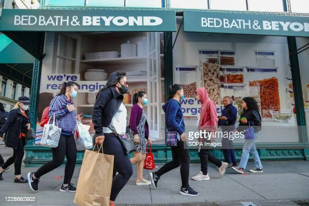 People wearing face masks walk past the Bed Bath & Beyond store. Bed Bath & Beyond has announced plans to permanently close about 200 stores over the...