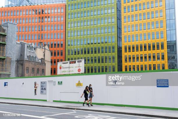People wearing face masks walk past the construction site behind the colourful Google offices building on 13th August 2020 in London, United Kingdom....