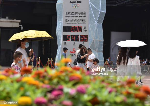 People wearing face masks walk past the countdown clock showing 200 days to the 2022 Olympic Winter Games. 2022 Beijing Winter Olympic Games are...