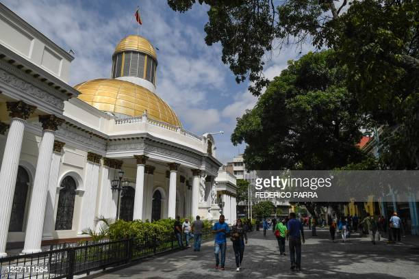 People wearing face masks walk past the National Assembly building after the government eased a nationwide lockdown as a preventive measure against...