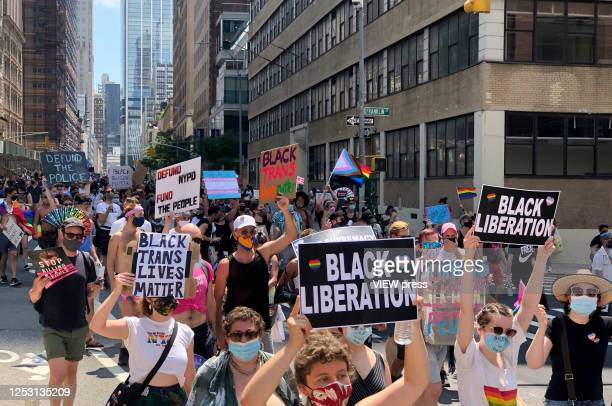 People wearing face masks walk through Manhattan during the Queer March for Black Lives on June 28, 2020 in New York City. The LGBTQ+ community...