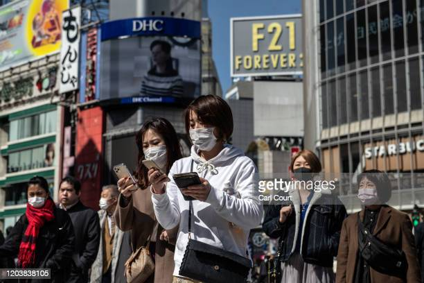 People wearing face masks walk through Shibuya on February 28 2020 in Tokyo Japan A growing number of events and sporting fixtures are being...