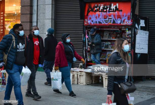 People wearing face masks walking past a newspaper stand on O'Connell Street in Dublin city center during Level 5 Covid-19 lockdown. On Thursday, 4...