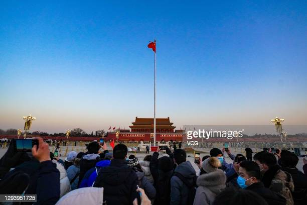 People wearing face masks watch the flag-raising ceremony at Tiananmen Square on New Year's Day on January 1, 2021 in Beijing, China.