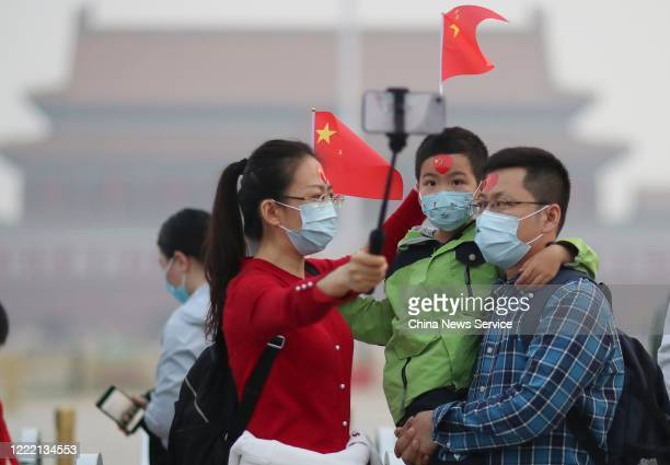 People wearing face masks watch the national flag-raising ceremony at Tiananmen Square on the International Workers' Day on May 1, 2020 in Beijing,...