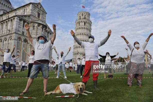 People wearing face masks while keeping social distances and a dog take part in a flash mob near the tower of Pisa on May 30, 2020 in Pisa, Italy....
