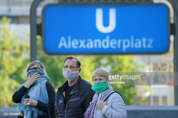 People wearing face masks, who said they did not mind being photographed, wait at a tram stop at Alexanderplatz on the first day of a nationwide...