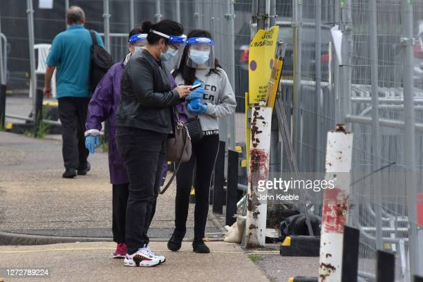 People wearing face shields masks and gloves arrive as one of them checks her phone at a walk in Covid19 testing facility on September 16 2020 in...
