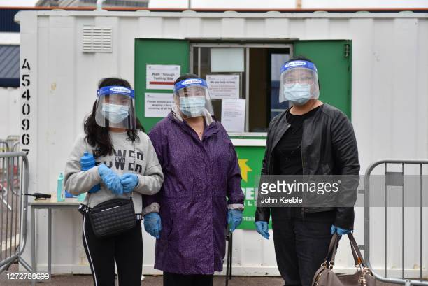 People wearing face shields masks and gloves pose as they arrive at a walk in Covid19 testing facility for a test on September 16 2020 in Southend on...