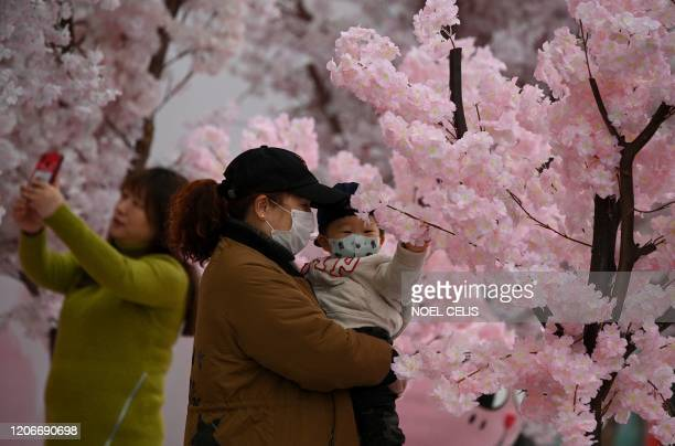 TOPSHOT People wearing facemasks are seen near a mall in Nanjing east China's Jiangsu Province on March 12 2020 The new coronavirus outbreak is a...