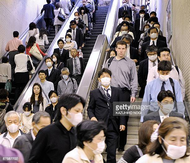 People wearing facemasks arrive at a railway station on way to their offices in Kobe, Hyogo prefecture, in western Japan on May 18, 2009. Japan...