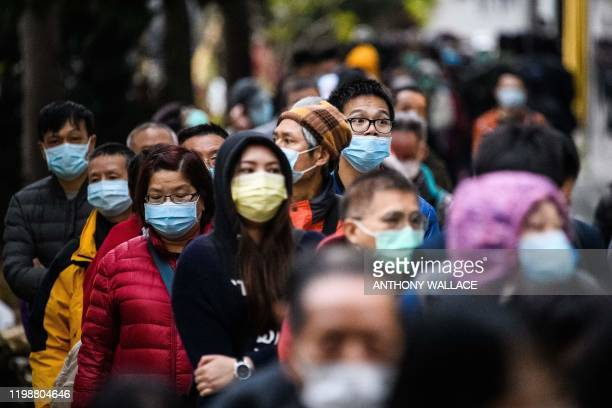 TOPSHOT People wearing facemasks as a preventative measure following a coronavirus outbreak which began in the Chinese city of Wuhan line up to...