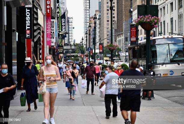 People wearing facemasks carry shopping bags as they walk near Herald Square on June 25, 2020 in New York City. - New York businesses opened their...