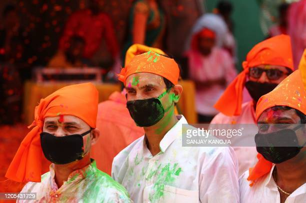 People wearing facemasks celebrate Holi, the spring festival of colours, during an event origanized by Trishla Foundation, a non-profit organisation...