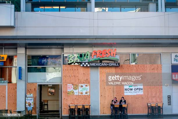 People wearing facemasks have lunch outside of a boarded Baja Fresh restaurant on Hollywood Boulevard amid the Coronavirus pandemic, November 10 in...