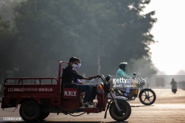 People wearing facemasks ride along a street amid smoggy condition in New Delhi on October 30, 2020.