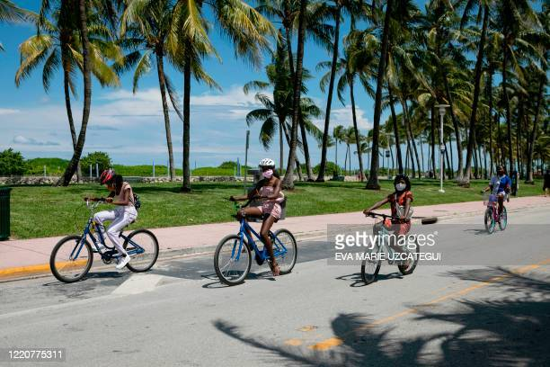 People wearing facemasks ride bicycles on Ocean Drive in Miami Beach, Florida on June 16, 2020. - Florida is reporting record daily totals of new...