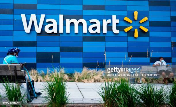People wearing facemasks sit outside a Walmart store in Washington, DC on July 15, 2020. - Walmart will require shoppers to wear face masks starting...