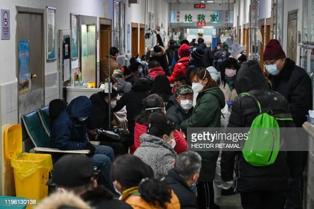 People wearing facemasks to help stop the spread of a deadly virus which began in the city wait for medical attention at Wuhan Red Cross Hospital in...