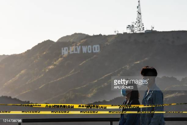 People wearing facemasks walk at the Griffith Observatory with a view of the Hollywood sign at the start of Memorial Day holiday weekend amid the...