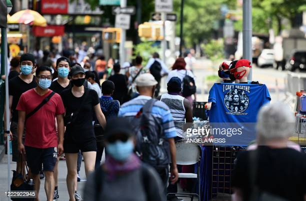 People wearing facemasks walk down a street near Union Square on June 25, 2020 in New York City. - New York businesses opened their doors to...