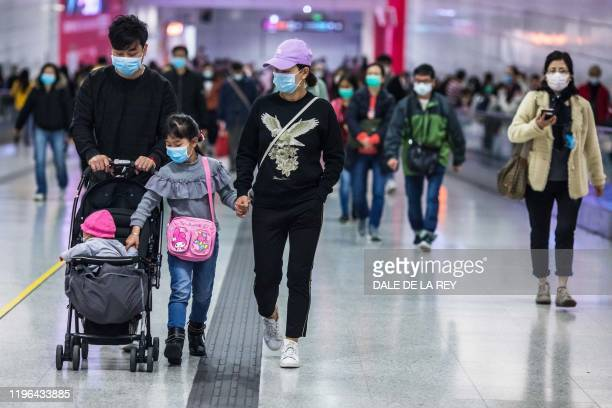 People wearing facemasks walk through a train station on the second day of the Lunar New Year of the Rat in Hong Kong on January 26 as a preventative...