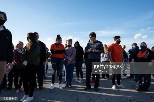 People wearing FedEx uniforms gather during a vigil to mourn the eight murdered FedEx Ground employees at Krannert Park on April 17, 2021 in...