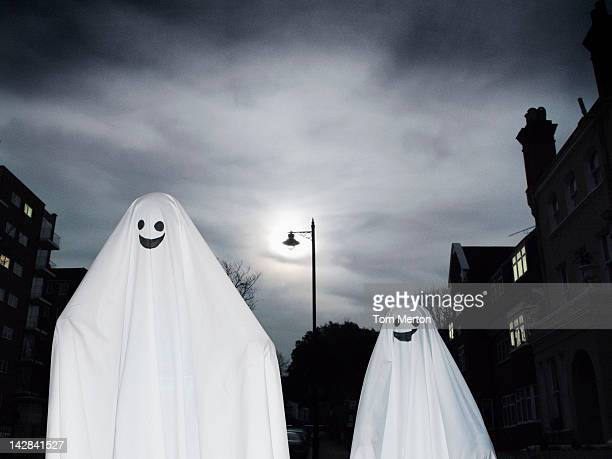 People wearing ghost costumes on city street