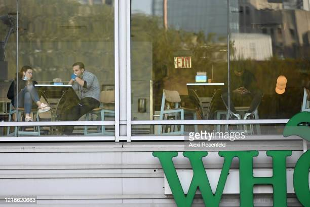 People wearing gloves and masks sit in the Whole Foods cafe in Union Square amid the coronavirus pandemic on April 12 2020 in New York City United...