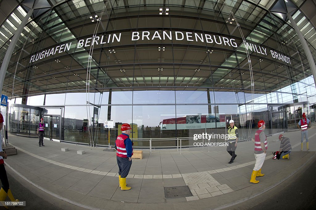 People wearing hard hats are seen outside the main entrance of the Berlin-Brandenburg International airport aka Willy Brandt Airport during a visit to the building site in Schoenefeld, near Berlin, on September 11, 2012, during the International Air Show ILA taking place nearby. For the fourth time in two years, the opening of the aiport to replace the German capital's two current hubs was put back in September 2012 to October 27, 2013. ANDERSEN