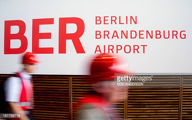 People wearing hard hats walk past a sign reading the name of the BerlinBrandenburg International airport aka Willy Brandt Airport in the check in...