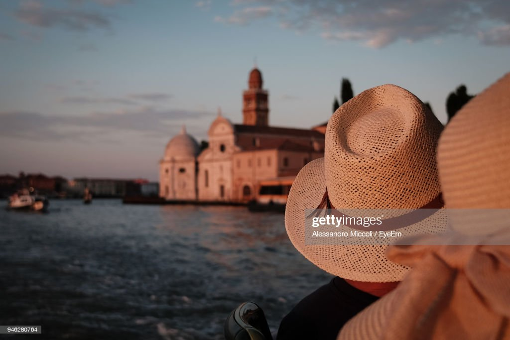 People Wearing Hat On Boat At River During Sunset : Stock Photo