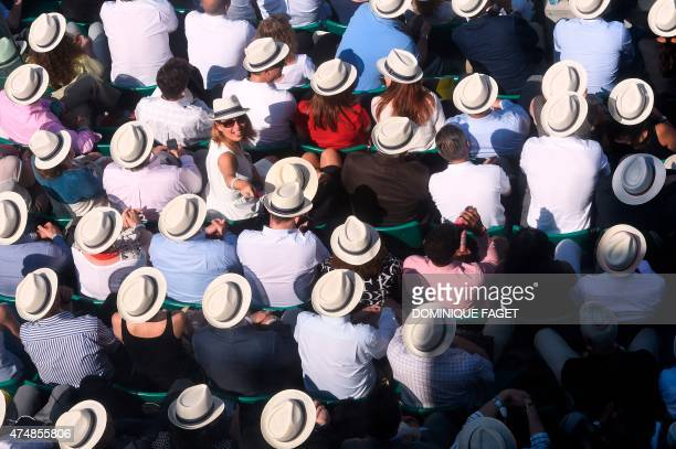 People wearing hats attend a match of the men's second round of the Roland Garros 2015 French Tennis Open in Paris on May 27, 2015. AFP PHOTO /...