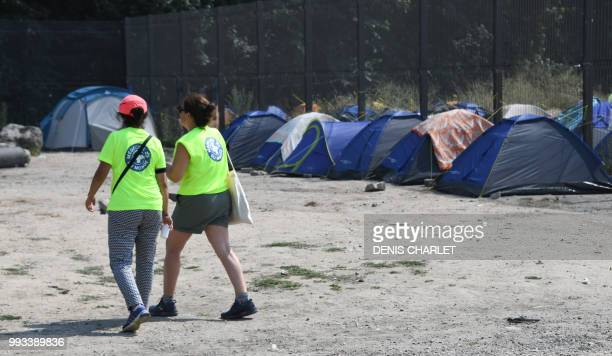 People wearing jacket of Medecin du Monde NGO walks by tents of migrants in Calais on July 7 2018 Several hundred people took part in a 'solidarity'...