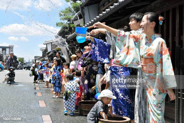 People wearing kimonos splash water in an attempt to cool down on July 21 2018 in Mino Gifu Japan Two highpressure systems are blanketing the...