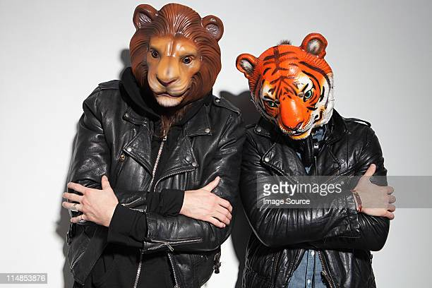 people wearing lion and tiger masks at party - lion feline stock pictures, royalty-free photos & images