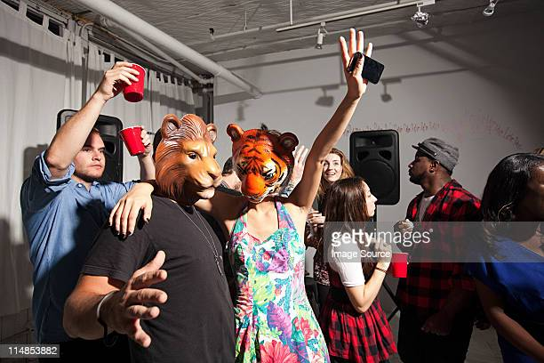 People wearing lion and tiger masks dancing at party