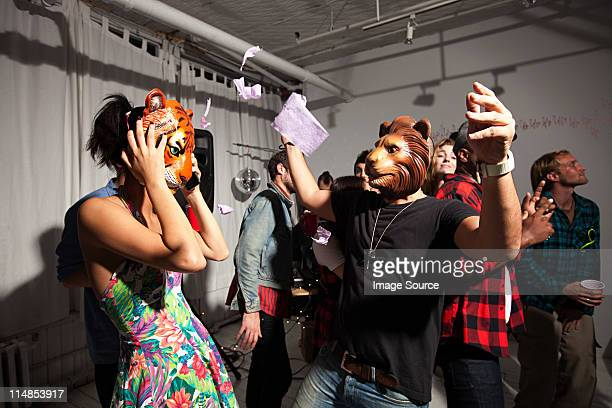 people wearing lion and tiger masks dancing at party - mask disguise stock pictures, royalty-free photos & images