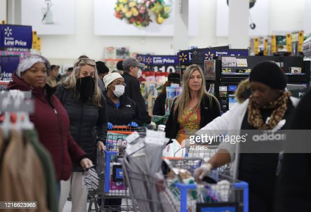 People wearing masks and gloves wait to checkout at Walmart on April 03, 2020 in Uniondale, New York. The World Health Organization declared...