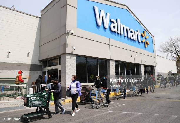 People wearing masks and gloves wait to enter a Walmart on April 17, 2020 in Uniondale, New York. The World Health Organization declared coronavirus...