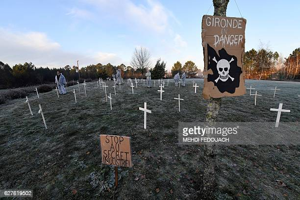 People wearing masks and protective suits stand next placards which translates as 'Gironde in danger' 'trade secret' and white crosses planted by...