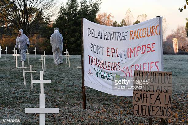 People wearing masks and protective suits stand next to banner which translates as 'period of 'entry' shortened EPI imposed wine workers...
