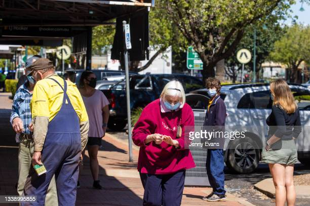 People wearing masks and socially distancing are seen lining up at a Pharmacy on September 08, 2021 in Narromine, Australia. New freedoms have been...