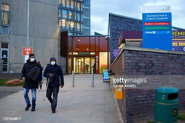 People wearing masks as a precautionary measure against covid19 leave Northwick Park Hospital in London on March 20 where they have declared a...