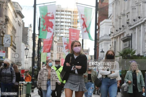People wearing masks because of the coronavirus pandemic are seen in the centre of Cardiff on October 23 hours before Wales goes into a two-week...