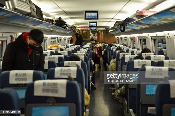 People wearing masks board a train in the direction of Wuhan City at Hongqioa train station as they head home for the Lunar New Year in Shanghai on...
