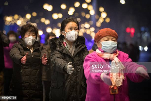 People wearing masks dance on a street on December 19 2016 in Beijing China At least 24 cities in North China issued red alerts on Friday warning...