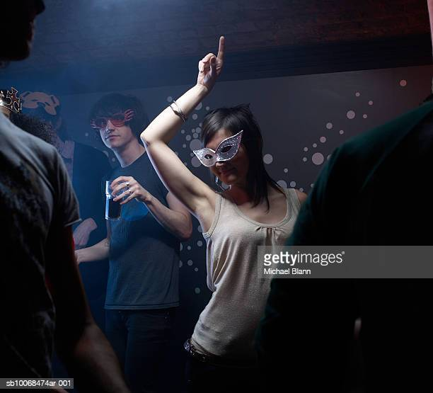 People wearing masks, dancing in night club