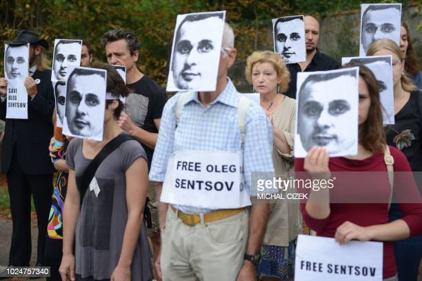 TOPSHOT People wearing masks depicting Ukrainian film director Oleg Sentsov take part in a protest on August 28 in front of the Russian embassy in...
